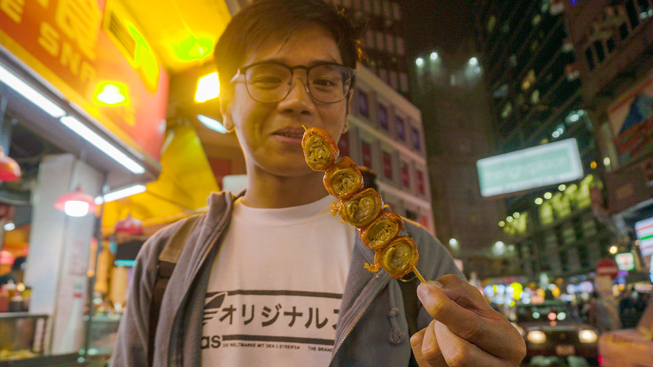 Wayne staring down a stick of pork intestines in Hong Kong